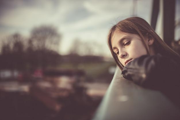 Droevig meisje dat zich op de brug bevindt
