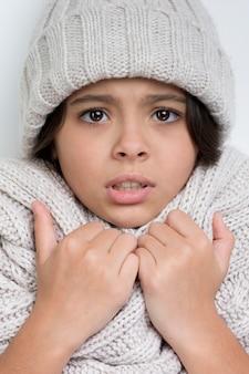 Droevig meisje met handen op de dikke sjaal