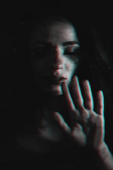 Droevig meisje met stromende mascara met glitch effect door het glas met regendruppels
