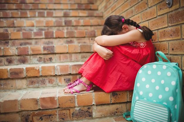 Droevig schoolmeisje met hoofd in haar benen