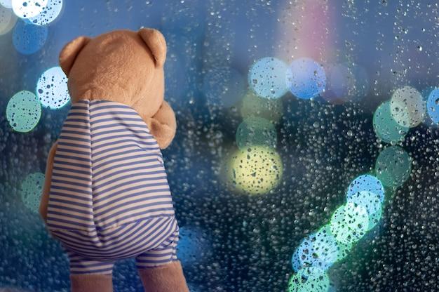 Droevig teddybeer die bij venster in regenachtige dag schreeuwt.