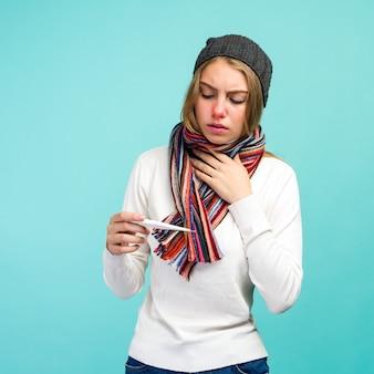 Droevig tienermeisje dat verwarmingspijp heeft die thermometer neemt