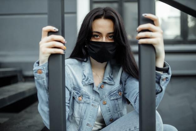 Droevig tienermeisje in medisch masker achter de tralies. scholen worden in quarantaine geplaatst vanwege ziekte, epidemieën. coronapandemie. covid 19