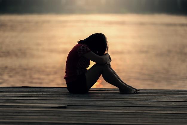 Droevig vrouwensilhouet dat bij zonsondergang ongerust wordt gemaakt