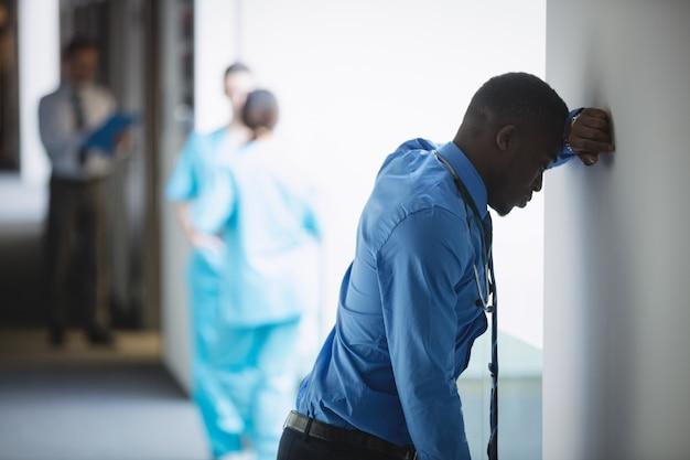 Droevige arts die op muur leunt