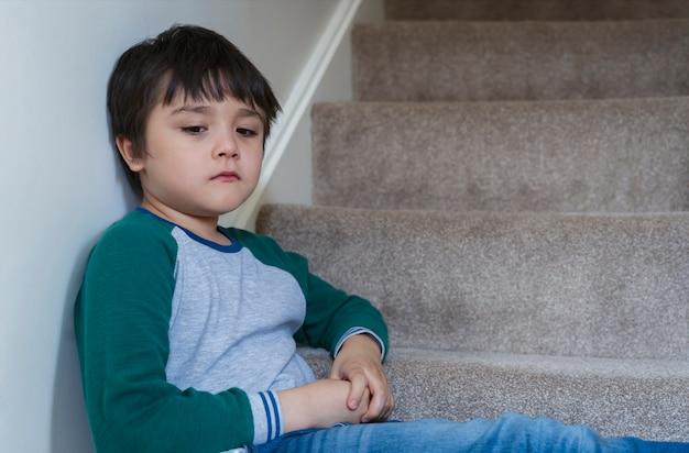 Droevige aziatische jongen zit 's ochtends alleen op de trap, eenzaam kind kijkt dow met een droevig gezicht niet blij om terug naar school te gaan, depressief kindjongen zit in de hoek van een trap, geestelijke gezondheid