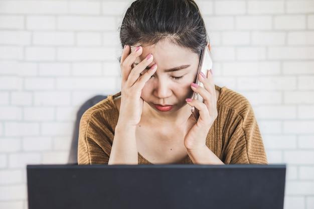 Droevige aziatische vrouw die op telefoon op het werkplaats spreekt