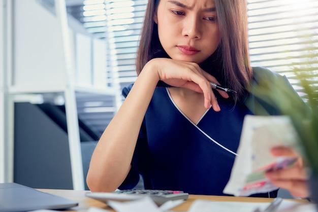 Droevige aziatische vrouwenhand die uitgavenrekening en berekening over schuldrekeningen maandelijks bij de lijst in huisbureau houden.