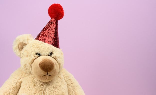 Droevige beige teddybeer in een rode pet zit op een paars oppervlak, een plek voor een inscriptie