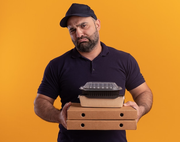 Droevige bezorger van middelbare leeftijd in uniform en pet die voedselcontainer op pizzadozen houden die op gele muur worden geïsoleerd