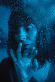 Droevige blik van een jonge vrouw die naar een regenachtige nacht in de quarantaine van de covid19 kijkt