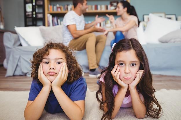 Droevige broers en zussen liggend op tapijt terwijl ouders zitten