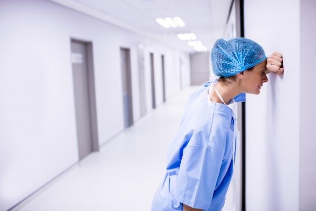 Droevige chirurg die op muur in gang leunt