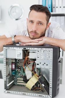 Droevige computeringenieur die op computer leunen