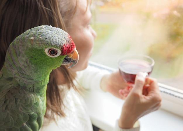 Droevige dame met een papegaai die bij het raam zit. dame in een depressie bij het raam.