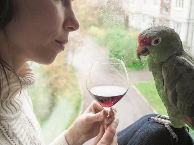Droevige dame met een papegaai die bij het raam zit