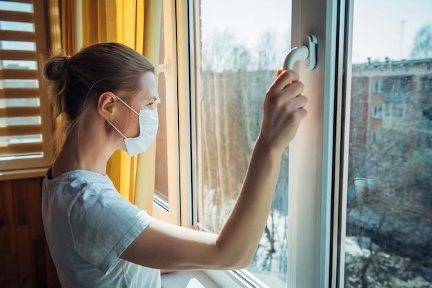 Droevige eenzame vrouw in beschermend medisch masker op haar gezicht dat venster bekijkt. quarantaine en coronavirus concept