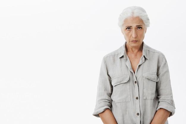 Droevige en sombere grootmoeder die er ongemakkelijk uitziet