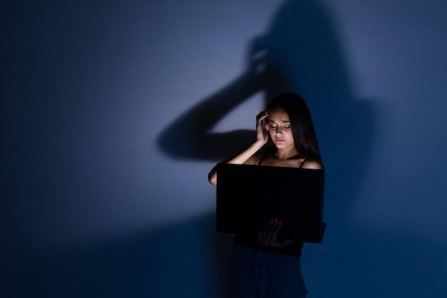 Droevige en vrouwelijke tiener met tabletcomputer en laptop die aan cyberpesten lijden a