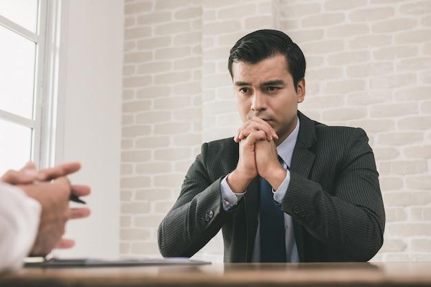 Droevige en wanhopige zakenman met handen op kin