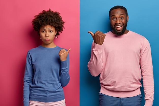Droevige etnische vrouw en gelukkige man wijzen hun duimen naar elkaar, hebben ruzie of ruzie