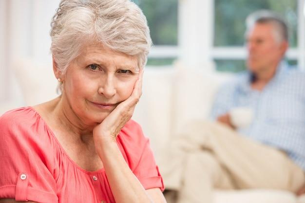 Droevige hogere vrouw na het debatteren met echtgenoot in woonkamer