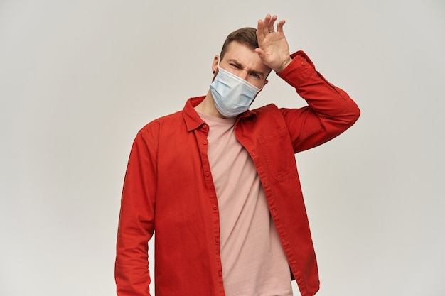 Droevige jonge bebaarde man in rood shirt en virusbeschermend masker op gezicht tegen coronavirus die zijn voorhoofd aanraakt en koorts controleert over witte muur
