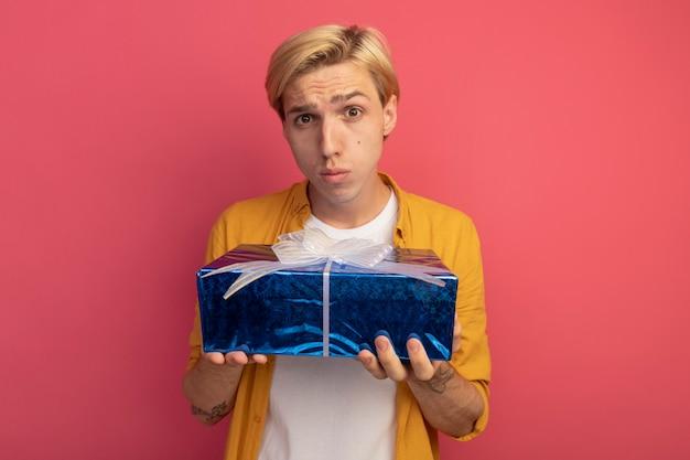 Droevige jonge blonde kerel die gele de giftdoos van de t-shirtholding draagt