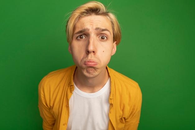 Droevige jonge blonde kerel die recht vooruit kijkt draagt geel t-shirt dat op groen met exemplaarruimte wordt geïsoleerd