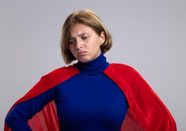 Droevige jonge blonde superheldenvrouw in rode cape die handen op taille houden die neer geïsoleerd op witte muur kijken