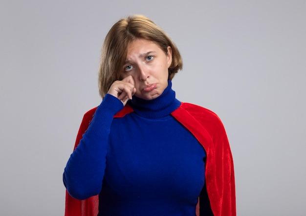 Droevige jonge blonde superherovrouw die in rode cape voorzijde afvegende tranen bekijkt die op witte muur met exemplaarruimte worden geïsoleerd