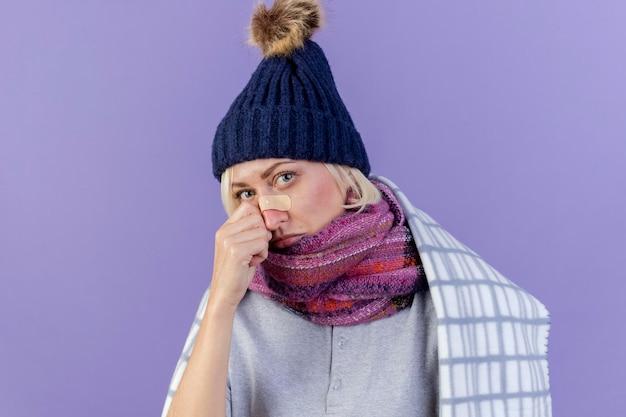 Droevige jonge blonde zieke slavische vrouw met medische pleister op neus die de winterhoed en sjaal draagt