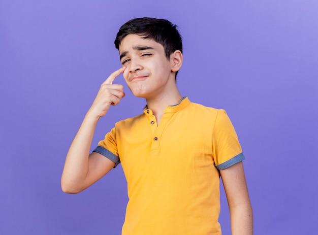 Droevige jonge kaukasische jongen die camera bekijkt die vinger onder oog zet die op purpere achtergrond wordt geïsoleerd