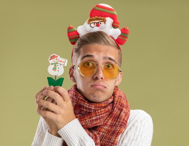 Droevige jonge knappe kerel die de hoofdband en de sjaal van de kerstman dragen die de sneeuwmanstuk speelgoed van de cameraholding bekijken dat op olijfgroene achtergrond wordt geïsoleerd