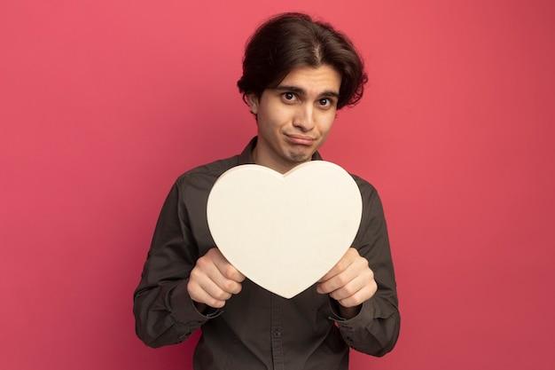 Droevige jonge knappe kerel die zwart t-shirt draagt dat hartvormgebaar houdt dat op roze muur wordt geïsoleerd