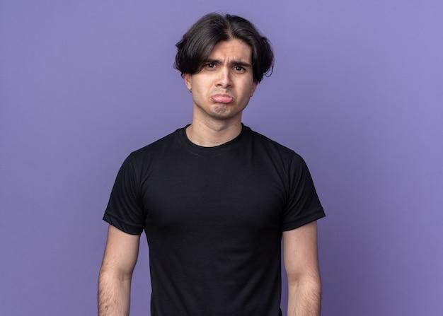 Droevige jonge knappe kerel die zwart t-shirt draagt dat op purpere muur wordt geïsoleerd