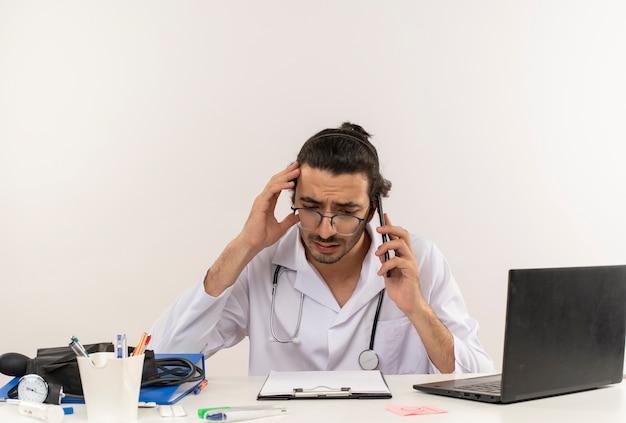 Droevige jonge mannelijke arts met medische bril die medische mantel met een stethoscoop draagt