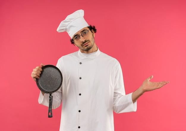 Droevige jonge mannelijke kok die eenvormige chef-kok en glazen draagt die koekenpan en punten met hand aan kant op roze houden