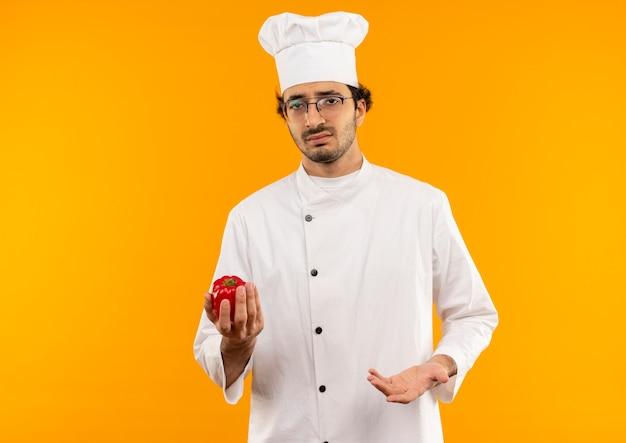 Droevige jonge mannelijke kok die eenvormige chef-kok en glazen draagt die peper houden die op gele muur wordt geïsoleerd