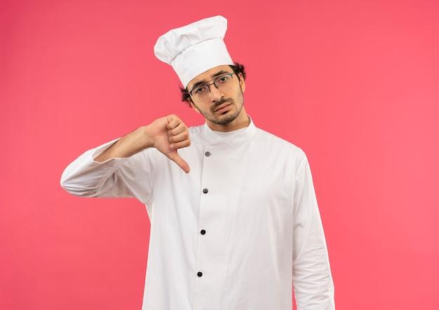 Droevige jonge mannelijke kok die eenvormige chef-kok en glazen zijn duim draagt die neer op roze muur wordt geïsoleerd
