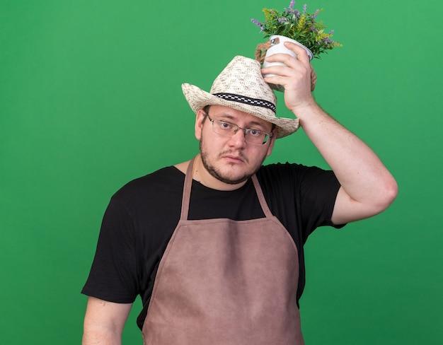 Droevige jonge mannelijke tuinman die tuinieren hoed draagt ?? die bloem in bloempot op hoofd houdt die op groene muur wordt geïsoleerd