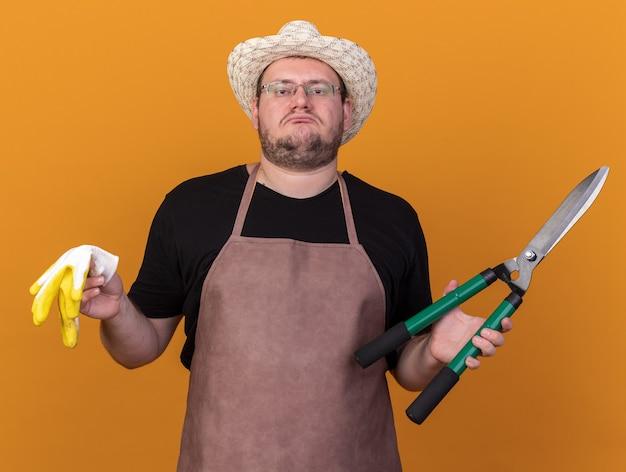 Droevige jonge mannelijke tuinman die tuinieren hoed draagt ?? die handschoenen met tondeuse houdt die op oranje muur worden geïsoleerd