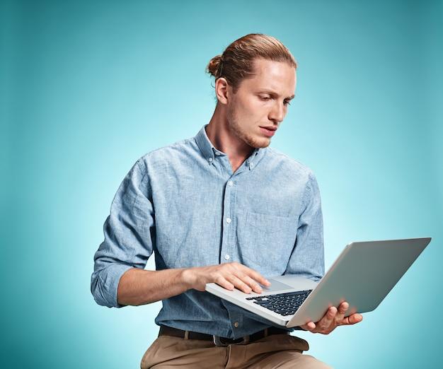 Droevige jonge mens die aan laptop werkt