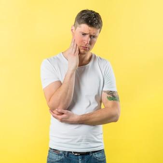 Droevige jonge mens die tandpijn heeft tegen gele achtergrond
