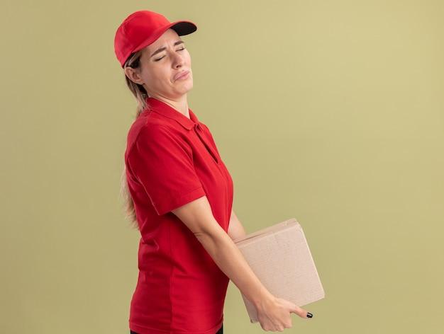 Droevige jonge mooie bezorgvrouw in uniform staat zijwaarts met kartonnen doos geïsoleerd op olijfgroene muur