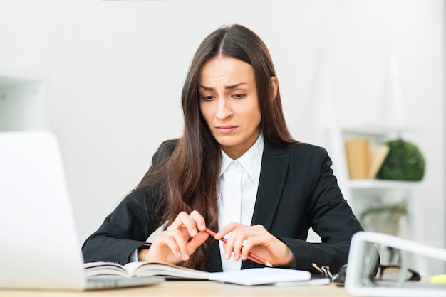 Droevige jonge onderneemster die rood potlood in haar handzitting bij bureau houdt
