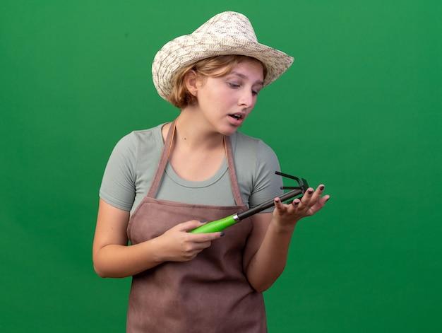 Droevige jonge slavische vrouwelijke tuinman die het tuinieren hoed dragen en schoffelhark op groen bekijken
