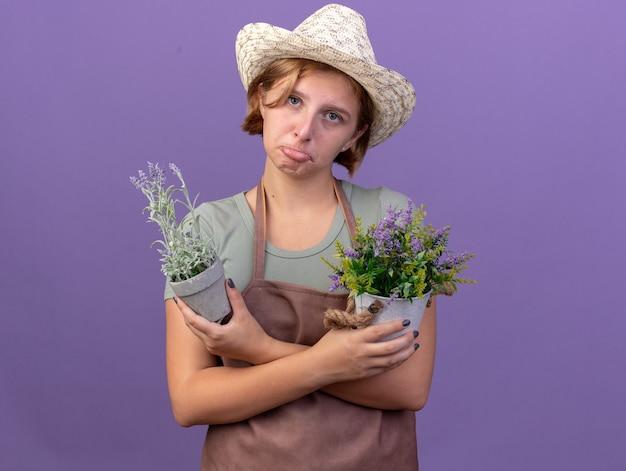 Droevige jonge slavische vrouwelijke tuinman die tuinieren hoed draagt die bloemen in bloempotten op paars houdt