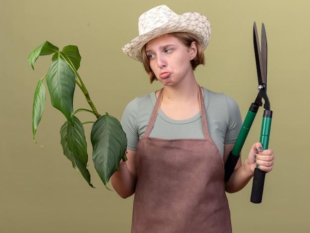 Droevige jonge slavische vrouwelijke tuinman die tuinierende hoed draagt die tuinierende schaar houdt en plant op olijfgroen