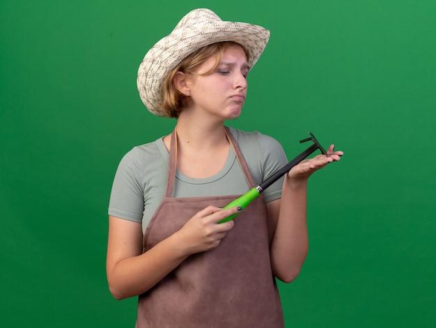 Droevige jonge slavische vrouwelijke tuinman die tuinierende hoed draagt houdt en bekijkt schoffelhark op groen